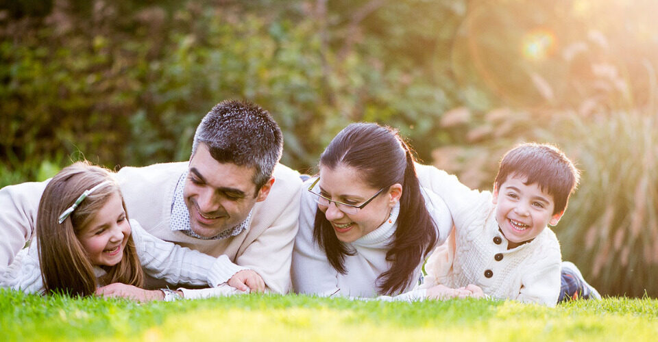 A mom, dad and child playing on the gradd - How to Prepare for a Family Photoshoot